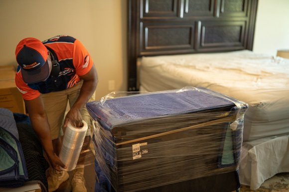 Movers carefully wrapping a dresser for a safe move